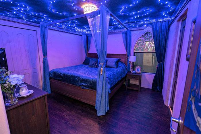 Hbaitación decorada con luces azules y cortinillas alrededor de la cama