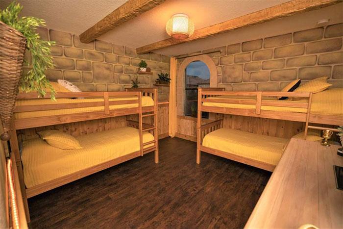 Recamara decorada con papel tapiz de ladrillo, literas de madera y cobijas amarillas