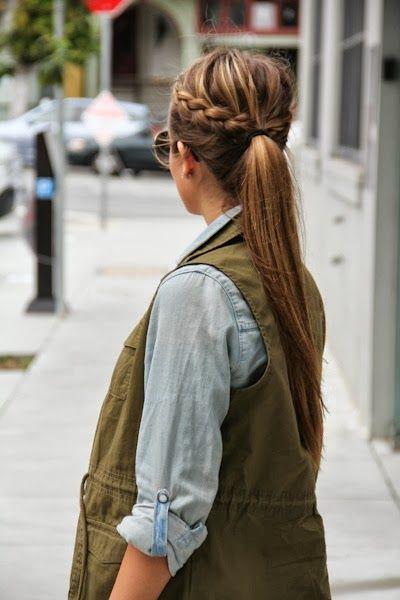 Chica de espaldas con chaleco verde militar y camisa azul cielo, peinado con coleta alta y media trenza lateral