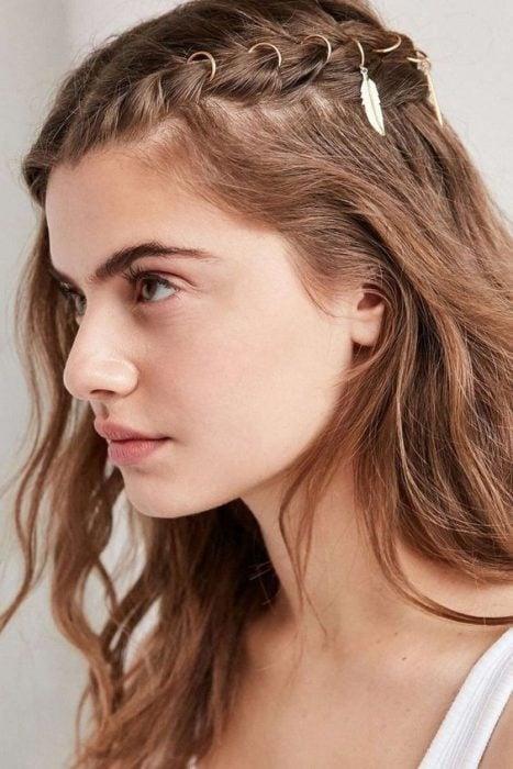 Chica posando de perfil con cabello suelto y una trenza lateral decorada con argollas