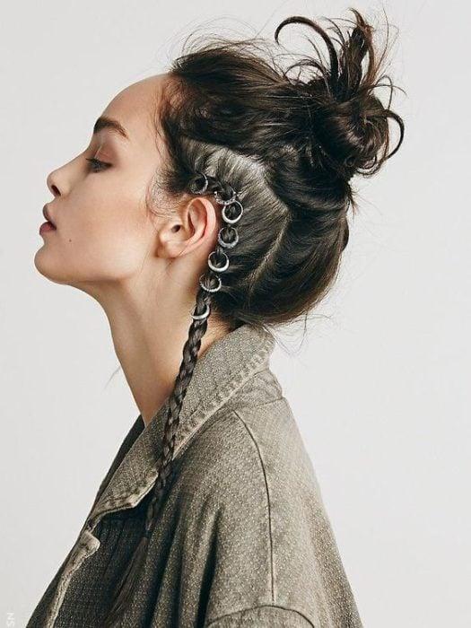 Chica posando de perfil con los ojos cerrados peinada con bun alto y una trenza lateral con argollas