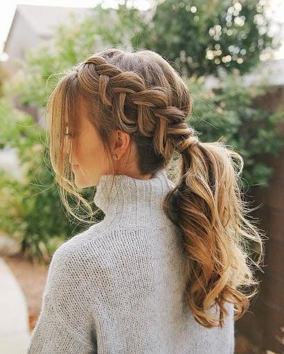Chica posando de lado mostrando su peinado en trenza lateral