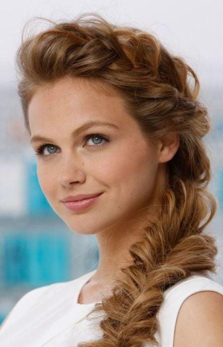 Chica sonriendo mostrando su peinado en trenza lateral