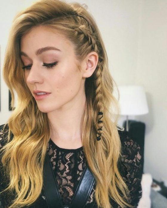 Chica con cabello rubio suelto en ondas y una pequeña trenza lateral