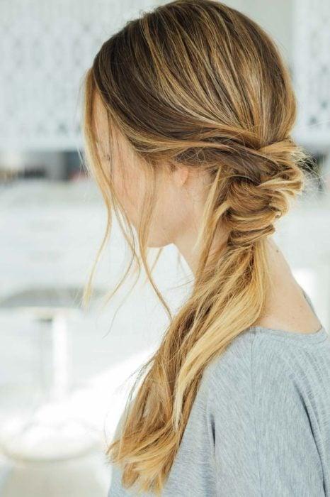 Chica volteada de espaldas mostrando su peinado de coleta baja con media trenza tejida
