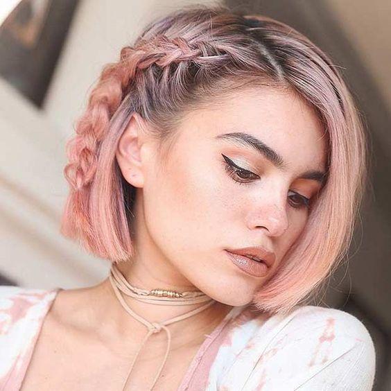 Chica de cabello corto teñido en rosa palo, posando de lado y mostrando un peinado de trenza lateral