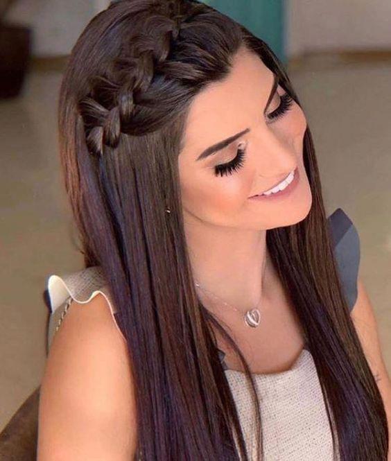 Chica sonriendo, mostrando su peinado de trenza al lado
