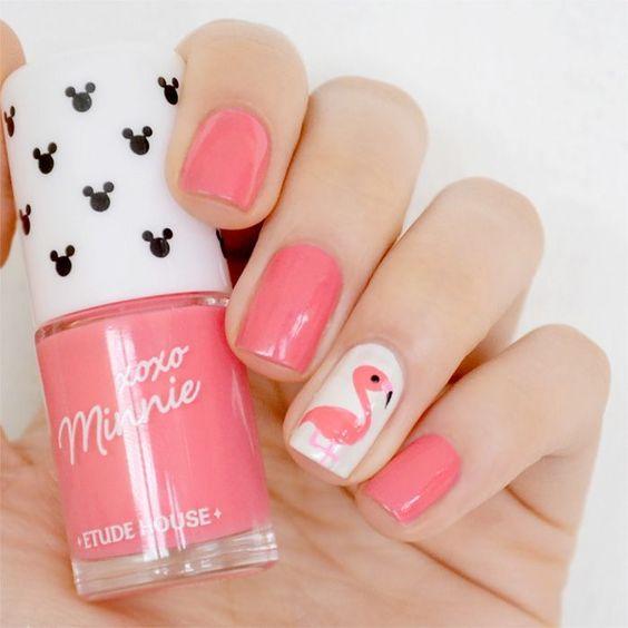 Manicura en tonos rosa con el diseño de un flamingo