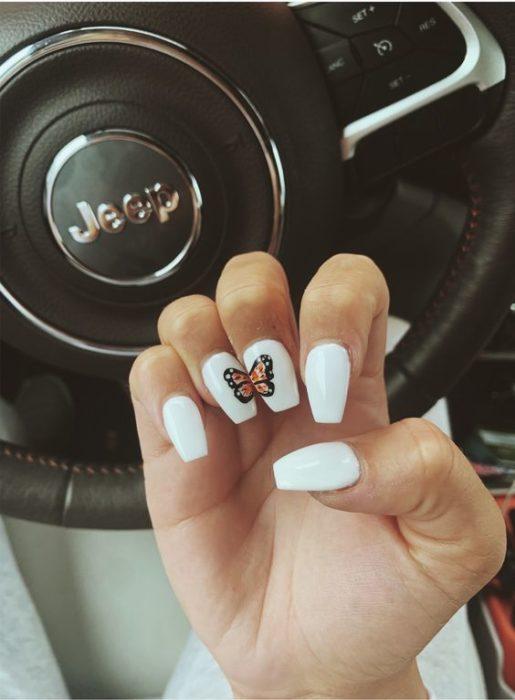 Manicura en tonos blancos con el diseño de una mariposa monarca