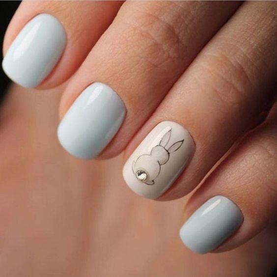 Manicura en tonos azules con una uña en gris claro y la silueta de un conejito