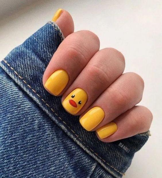 Manicura en color amarillo simulando un pato como decoración