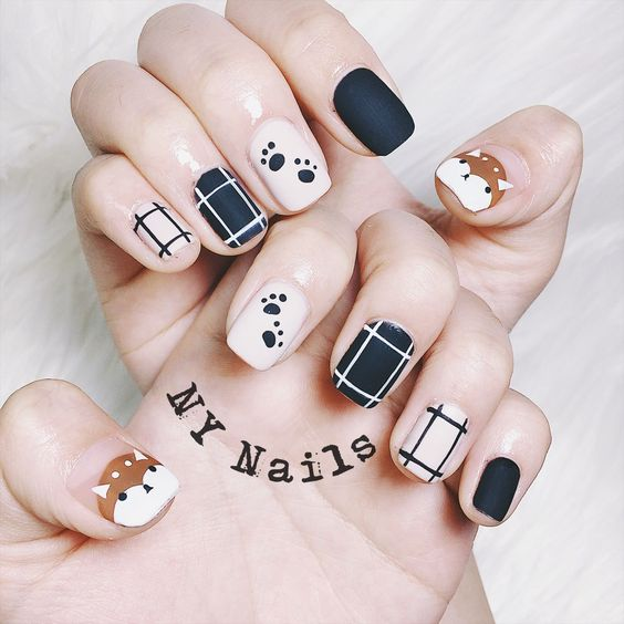 manicura en tonos neutros con decoración de perritos en color café