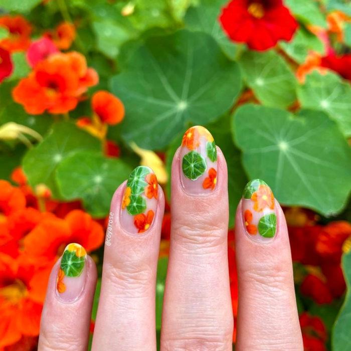 Manicura de flores; uñas con diseño de flor capuchina, tropaeolum anaranjadas