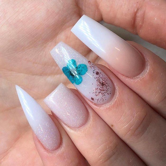 Uñas asimétricas blancas con toques flores