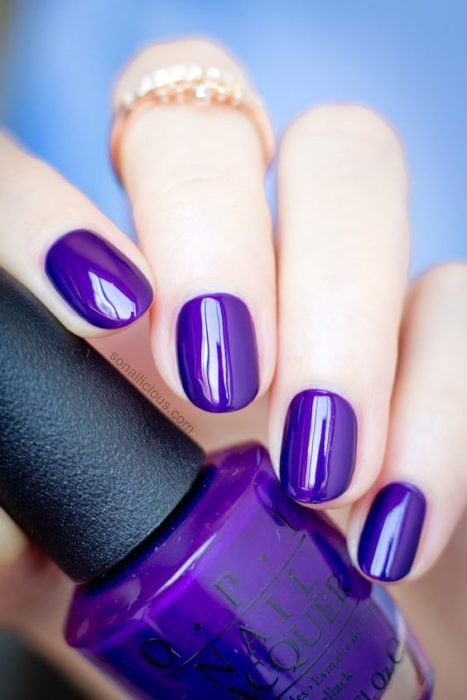 woman hands with manicure in purple grape tone with glitter