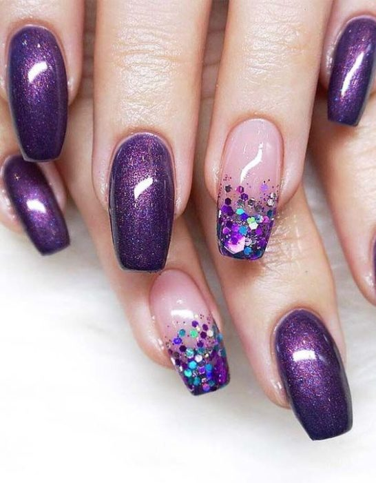 woman's hands with manicure in purple tones with glitter effect and tips with sparkles