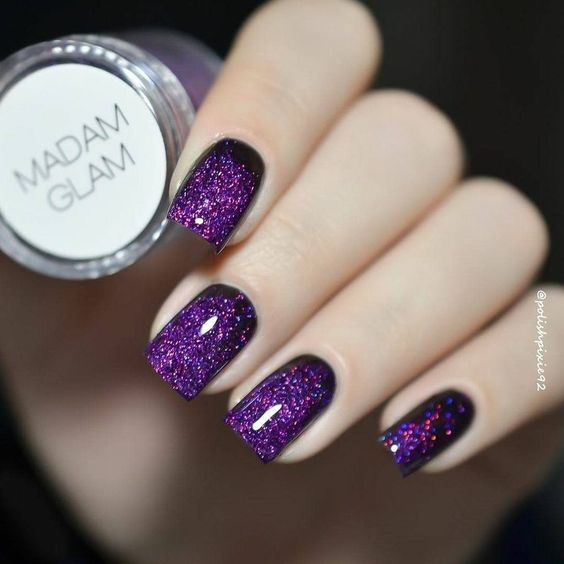 woman's hands with manicure in purple with glitter effect