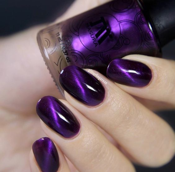 woman's hands with manicure in shades of purple and black with cat's eye effect
