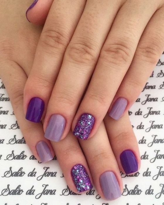 woman's hands with manicure in shades of purple, purple and purple with sparkles of glitter