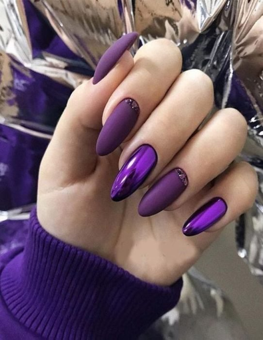 woman's hands with manicure in purple tones with metallic effect and in almond style