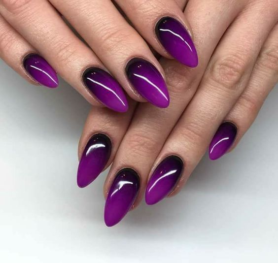 woman hands with manicure in purple tones with gradient effect in almond style