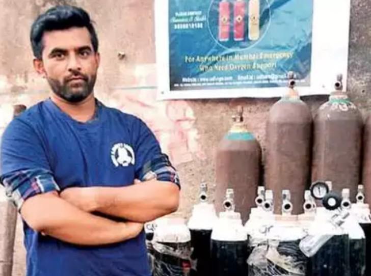 Hombre con brazos cruzados posando frente a diversos tanques de oxigeno que serán donados