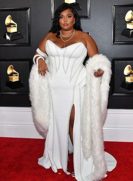 Lizzó usando un vestido de color blanco con aplicaciones de pedrería en color plateado en la gala de los Grammy