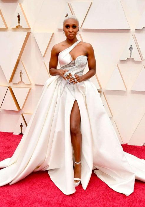 Cynthia Erivo con un vestido blanco y aplicaciones en plateado durante la alfombra roja de los premios Oscar 2020