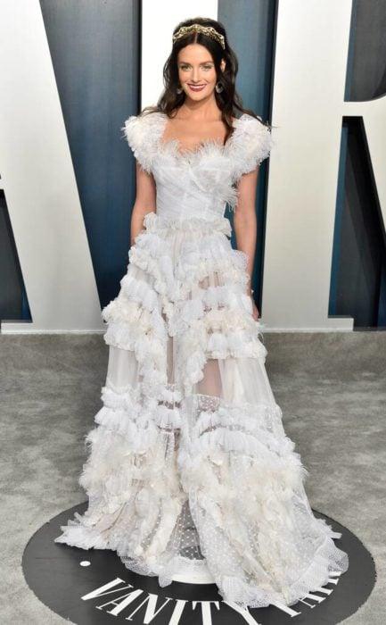 Lydia Hears usando un vestido blanco con encajes durante el after party de los premios oscar 2020