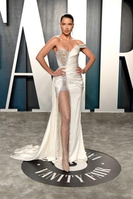 Adriana Lima usando un vestido blanco con abertura hasta el muslo durante la after party de Vanity Fair Oscar 2020