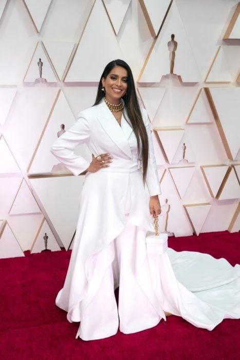 Lily Singh usando un pantalón y una chaqueta de color blanco con una cauda larga y un bolso cuadrado del mismo color durante los Óscar 2020