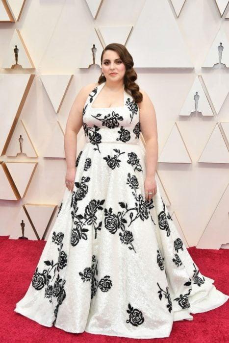 Beanie Feldstein usando un vestido largo de color blanco con un bordado de flores en color negro