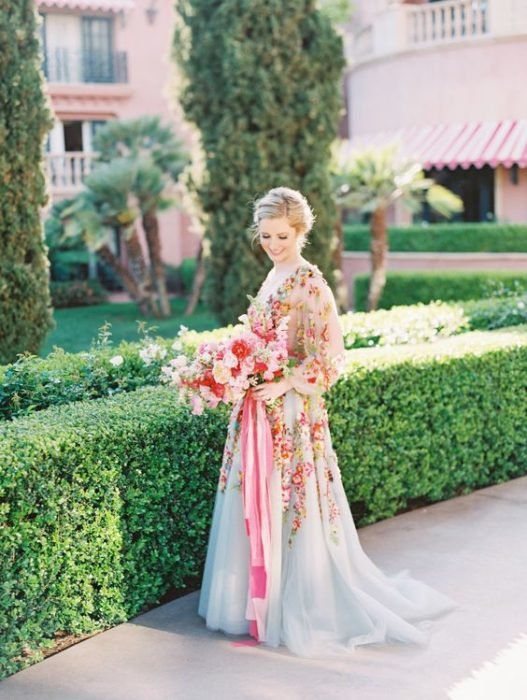 Bride in blue dress full of flowers holding a bouquet