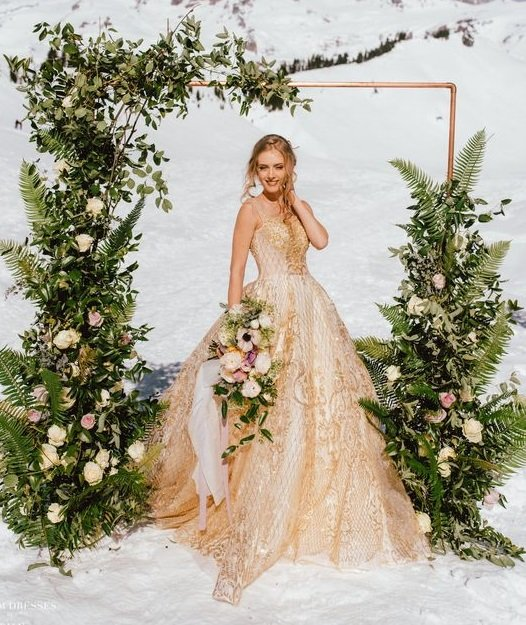 Blonde bride with golden dress in the snow