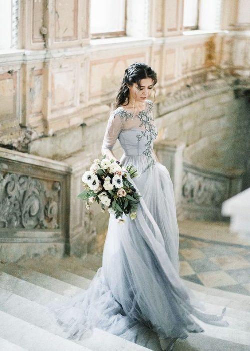 Bride posing on steps in gray wedding dress