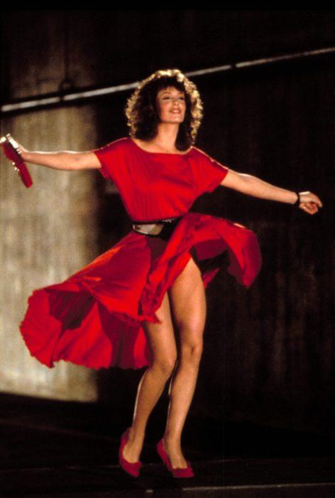 Kelly LeBrock en La mujer de rojocaminado sobre la calle mientras su vestido de color rojo vuela