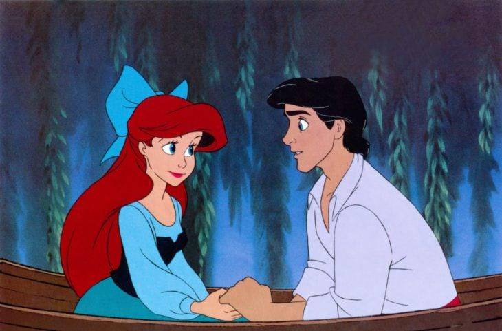Escena d ela película La Sirenita de Disney, Ariel y Eric tomados de las manos sobre una lancha de madera