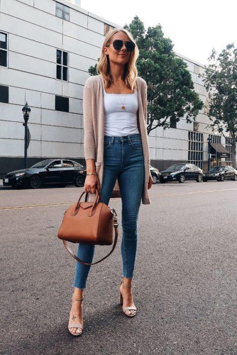 Chica con jeans, blusa blanca, cardigan beige y sandalias de tacón