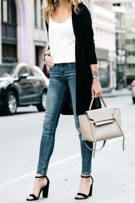 Mujer con jeans, blusa blanca, cardigan negro, bolso beige y sandalías negras de tacón