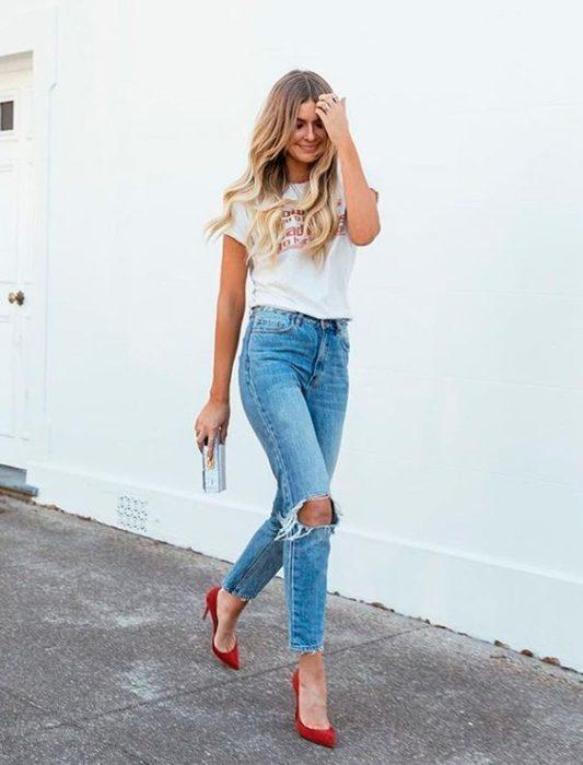 Chica rubia de cabello largo con jeans, blusa blanca y stilettos rojos