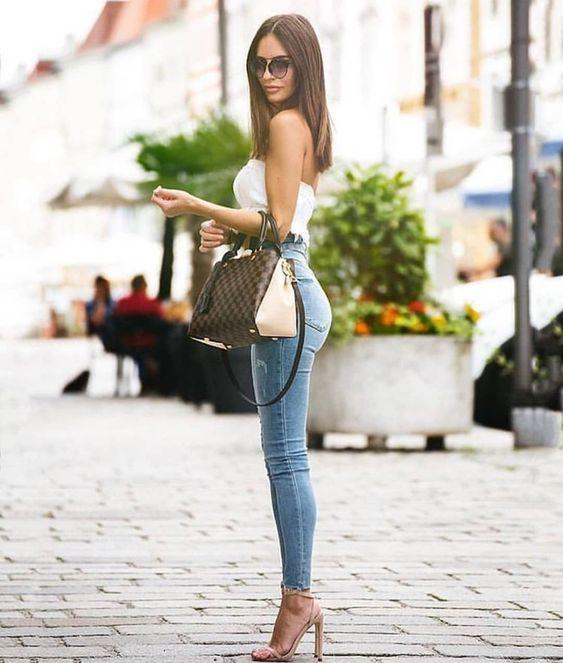 Chica con jeans, blusa blanca, bolso verde y sandalias beige de tacón