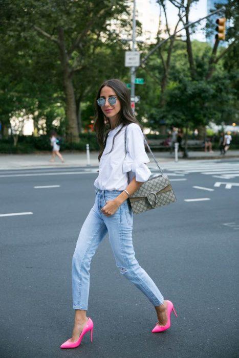Chica cruzando la calle con pantalón de mezclilla, blusa blanca y stilettos rosas