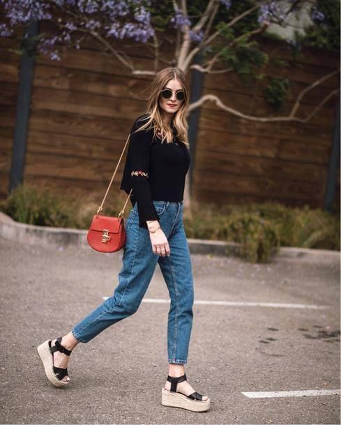 Chica con outfit de mezclilla., blusa negra y zapatos wedges