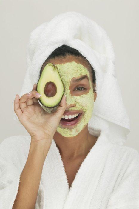 chica llevando mascarilla de aguacate dobre el rostro y una toalla enredada en la cabeza