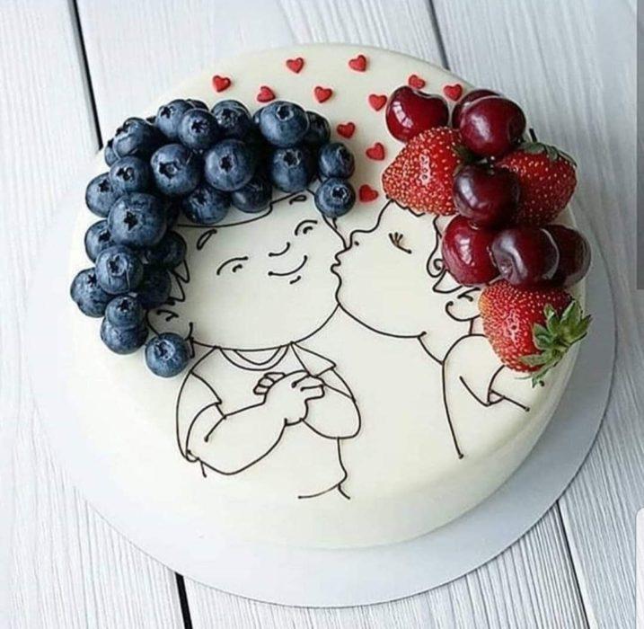 Pastel con betún blanco decordo con la silueta de niños con cabello rizado formado con fresas y uvas