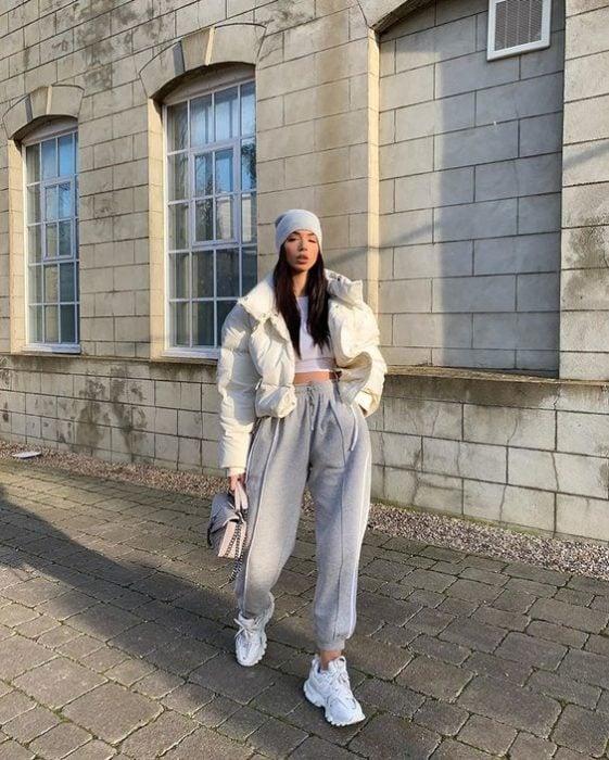 chica de cabello castaño largo usando una gorra gris, camisa blanca, abrigo blanco, pantalones deportivos pants grises, tenis blancos y bolsa de mano gris