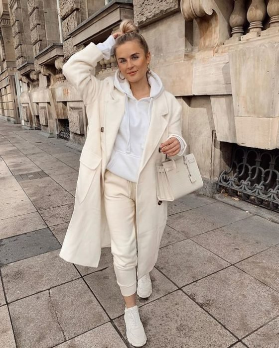 blonde girl wearing a white sweatshirt, beige sports coat and pants, white tennis shoes and beige leather handbag