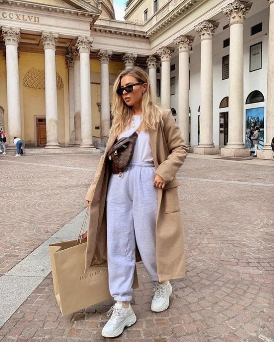 blonde girl with sunglasses, shopping, wearing a leather crossover bag, white T-shirt, beige coat, gray pants and white sports tennis shoes