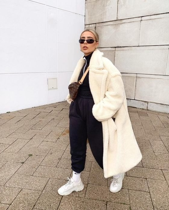 girl wearing white teddy coat, black top with high neck, sunglasses, black pants and white sports sneakers