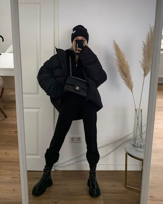 blonde girl taking a selfie in a black beanie, black oversized jacket, black top, black leather bag, black pants and leather boots